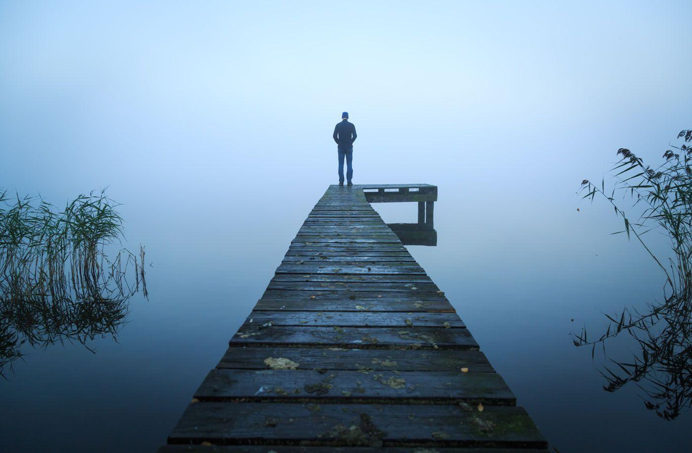 person på bro ved sø