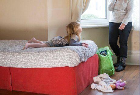 barn på seng med mor